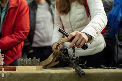 Obraz na plátně The girl disassembles the Kalashnikov assault rifle