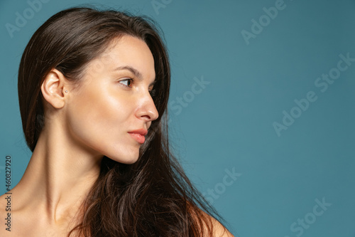 Wallpaper Mural Close-up portrait of young beautiful girl without makeup isolated over blue studio background