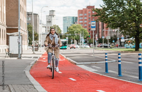 traffic, city transport and people concept - happy smiling woman riding bicycle along red bike lane or two way road on street