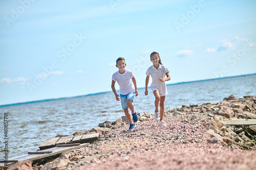 Photo Two kinds running on a beach and feeling great