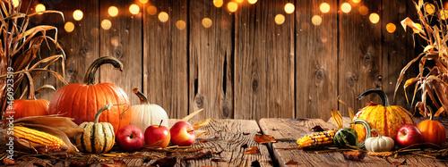 Fotografija Pumpkins Apples And Corn On Rustic Harvest Table With Bokeh Lights - Harvest And