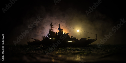 Silhouettes of a crowd standing at blurred military war ship on foggy background Fototapet