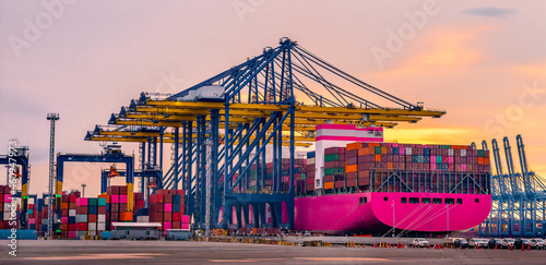 Obraz na plátně Container crane cargo freight ship with working crane loading bridge containers in shipyard at dock yard for logistic import and export transportation background