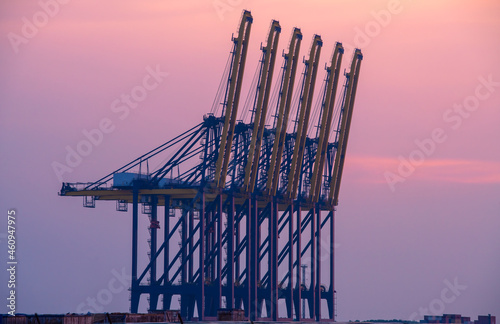 Canvas Container crane cargo freight ship with working crane loading bridge containers in shipyard at dock yard for logistic import and export transportation background