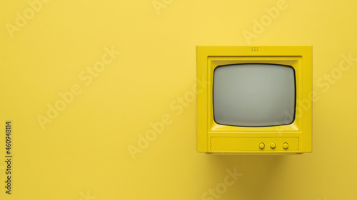 Fotografering Stylish image of a yellow TV on a yellow background