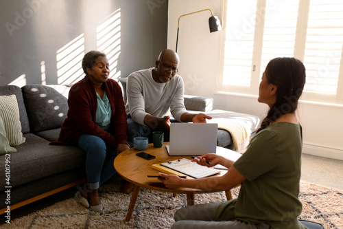African american senior couple having meeting with asian female financial advisor at home