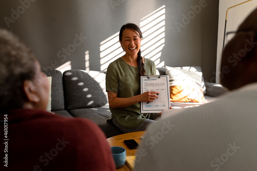 African american senior couple having meeting with happy asian female financial advisor at home