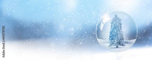 Obraz na plátně Schneekugel mit Tannenbaum vor unscharfem Hintergrund