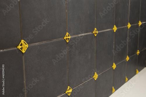 Pose d'un carrelage mural noir dans une salle de bains Fototapeta