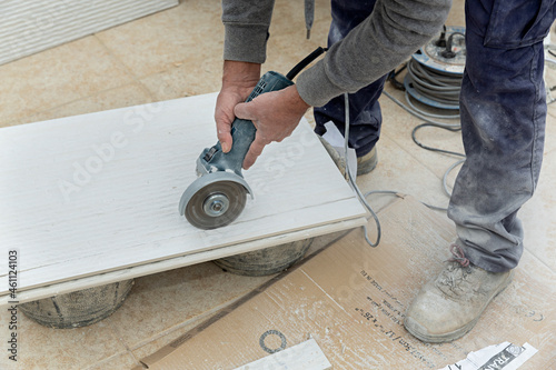 Fotografie, Obraz Albañil cortando una baldosa de cerámica con la radial.