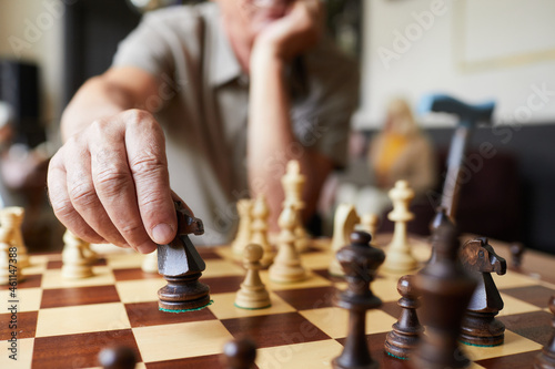Billede på lærred Close up of Caucasian senior man playing chess and enjoying activities in nursin