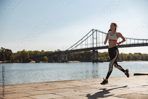 Canvas-taulu Cheerful sportswoman in tracksuit and sneakers runs along city embankment