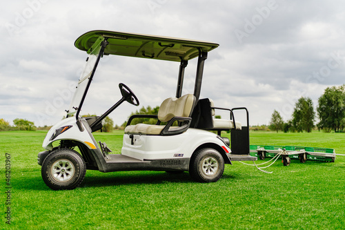 an electric car with a trailer for collecting balls on the golf course.
