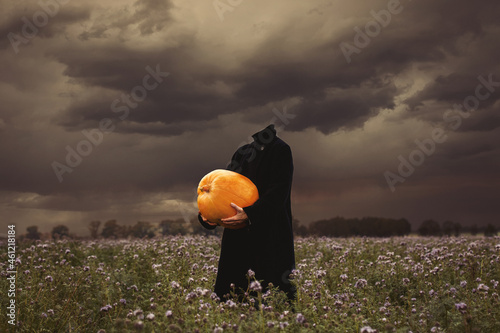 Photo Female in coat without a head holding pumpkin on flowers mead in rainy day