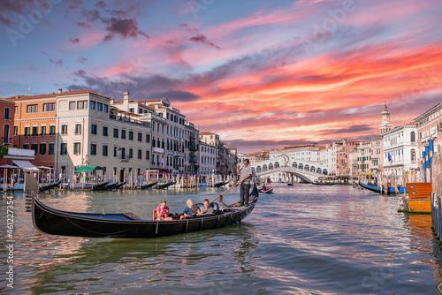 Tablou Canvas Venetian gondolier punting gondola through Grand canal waters of Venice Italy near Rialto bridge