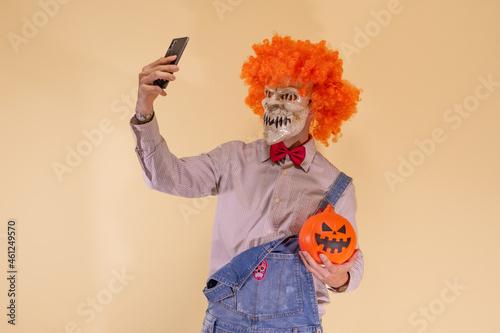 Obraz na plátne Payaso diabólico con la calabaza de Halloween, y haciéndose un selfie con el teléfono móvil, en fondo marrón con espacio para texto