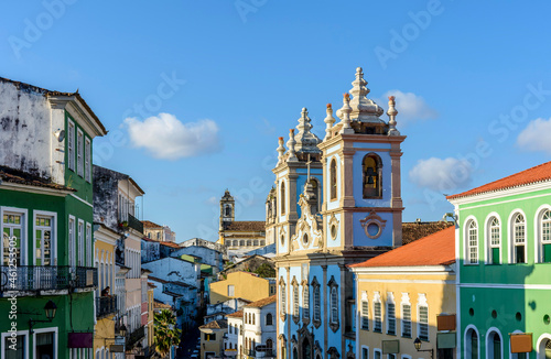 Foto Colorful and ancient colonial houses facades and historic church towers in baroq