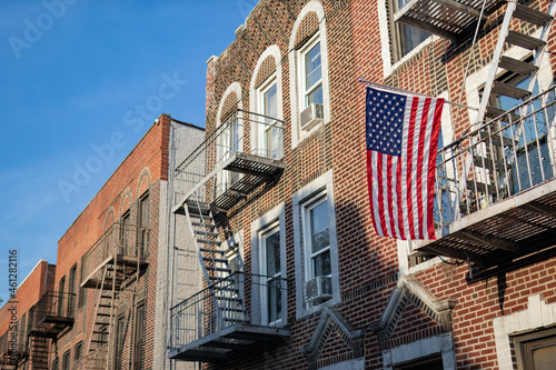 Fotografiet American Flag hanging from a Fire Escape along a Row of Old Brick Apartment Buil