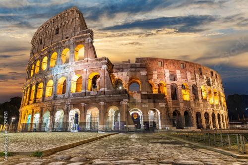 Illuminated Roman Coliseum under the clouds at sunrise, Italy Fototapeta