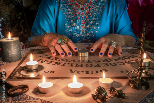 Fototapeta Ouija board with the hands of a fortune teller on the table