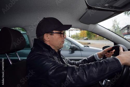 Fotomural A young driver wearing glasses, a leather jacket and a cap sits behind the wheel