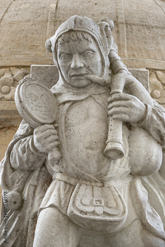 Fotografia, Obraz Ancient statue of buffoon or jester at the back of Magdeburger Roland Knight statue in front of Old City Hall (Rathaus), Magdeburg, Saxony Anhalt, Germany, closeup, details