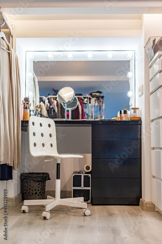 Fototapeta Feminine dressing table with lighting mirror cosmetics and accessories for getti