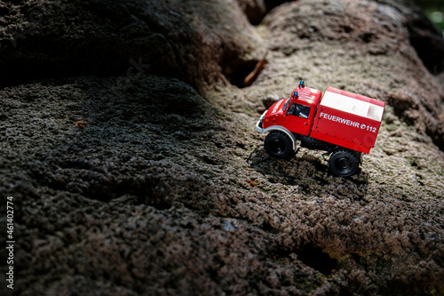 Fototapeta A red firefighting toy truck is placed on the surface of irregular bumpy rock fo