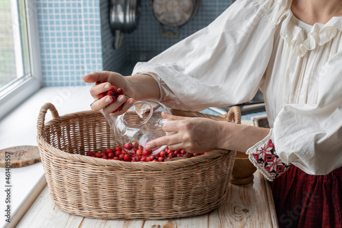 Obraz na plátně A girl in ethnic clothes in the kitchen, puts berries in a glass teapot