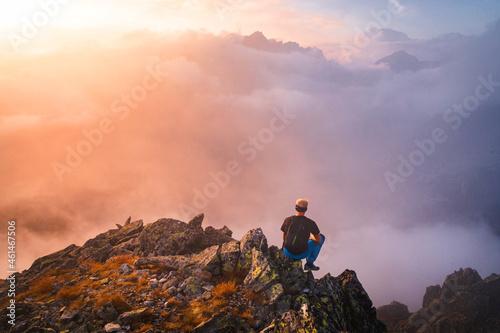 Hiker in black sit alone on the rock summit Fotobehang