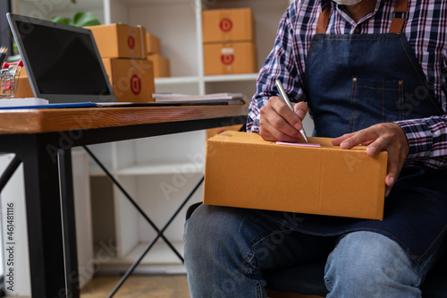Fotografia Starting small businesses SME owners man entrepreneurs working, box and check online orders to prepare to pack the boxes, sell to customers, sme business ideas online