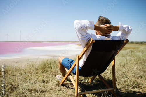 Businessman sitting in deck chair at beach of pink sea on sunny day Fotobehang