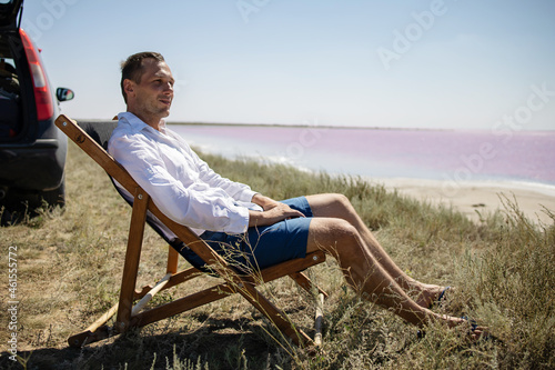 Foto Businessman sitting in deck chair at beach of pink sea on sunny day