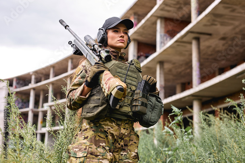 Fototapeta Military lady woman in tactical gear posing for photo in grass next to abandoned building
