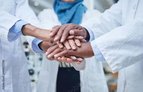Fotografering Shot of a group of unrecognisable scientists joining hands in solidarity in a la