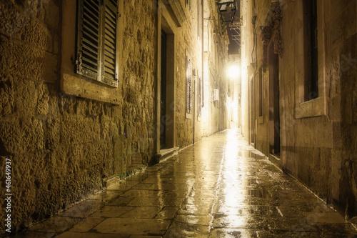 Billede på lærred Old alleyway with lights through a building