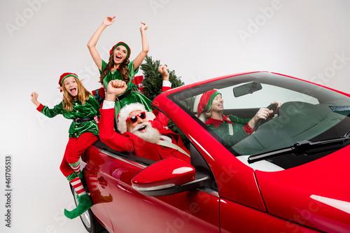 Murais de parede Photo of crazy stylish people prepare x-mas ride car deliver presents wear costu