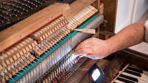 Foto Of professional worker repairing and tuning an old English bayonet piano