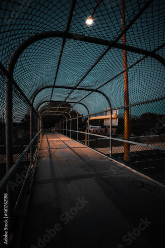 Empty caged footbridge at night - lines and shadows Fototapet