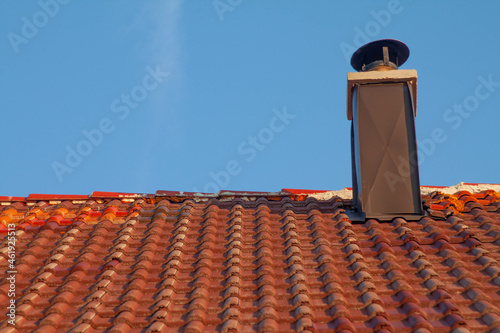 Canvastavla Rooftop with tiles and a chimney against a blue sky background