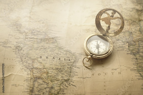 Fotografiet Retro style antique golden compass (sundial) and old nautical chart close-up