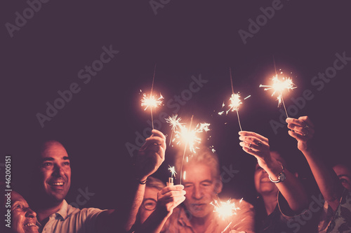 Family celebrating holding burning sparkles with arms raised. Group of multi generation family celebrating a birthday or anniversary or new year. Men and women having fun together
