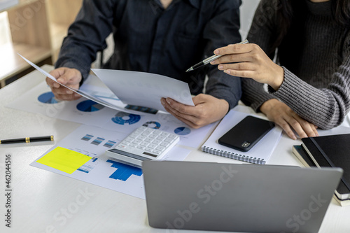 Fotografia, Obraz Meeting room of a startup company where two businessmen are looking at financial information from documents, they are meeting on monthly finance topics