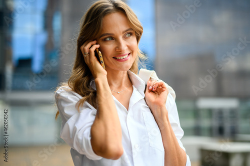 Cheerful young woman on the phone outdoor in a modern urban setting
