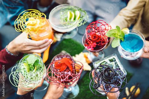 Billede på lærred People hands toasting multicolored fancy cocktails - Friends having fun drinking
