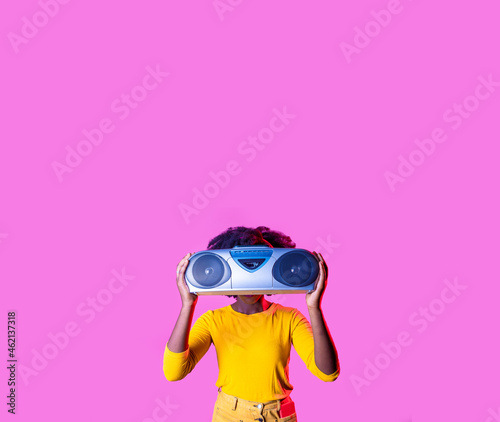 Young black woman listening music hiding holding vintage boombox isolated copyspace cropped background