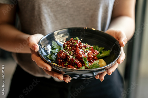 Fotografie, Obraz Girl holding a bowl of marinated chicken in spicy sauce with daikon