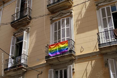 Balcon avec drapeau arc en ciel sur façade de pierre Fototapet