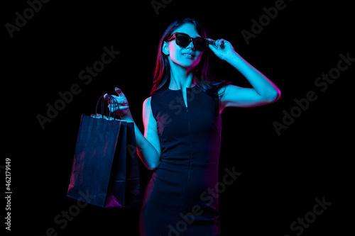Portrait of young woman in neon light on dark backgound. Human emotions, black friday, cyber monday, purchases, sales, finance concept.