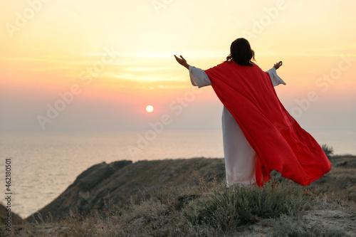 Jesus Christ raising hands on hills at sunset, back view Fotobehang